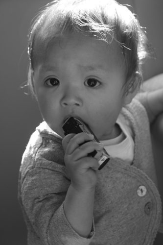 Human baby with a toy in his/her mouth