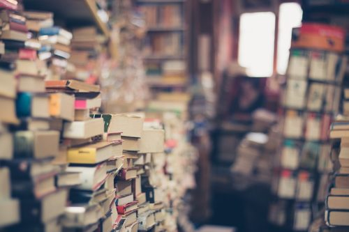 A bookshop with stacks and stacks of old books on the perimeter of the walls