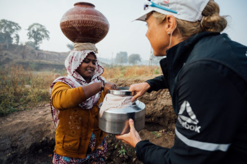 Ultra runner and water campaigner, Mina Guli helps a local woman collect water near Dahod, India during the #RunningDry Expedition, on 1 December 2018