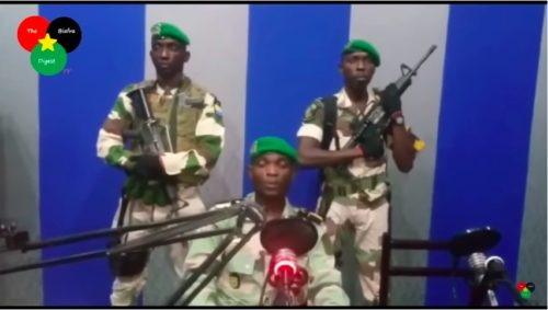 Three soldiers attempting a coup face the camera. One reads the message. Behind are two others with automatic weapons.