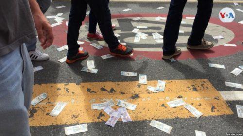 Worthless Bolivars strewn on the ground, ignored. Bolívares devaluados tirados en el piso durante la protesta como símbolo de la hiperinflación y la crisis económica que atraviesa Venezuela.
