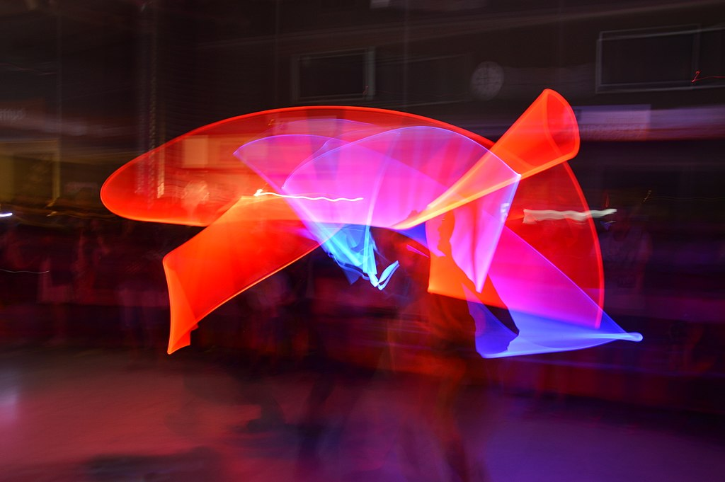 As the two fighters simulate a duel with lightsabers, the light paints its way on the long exposure photo. The red light appears much more prominent than the white light.