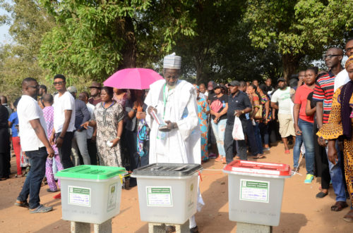 The Commonwealth Observer Group, chaired by the former President of the United Republic of Tanzania Jakaya Kikwete, witnessed the general elections in Nigeria. A man votes as others wait in lines.