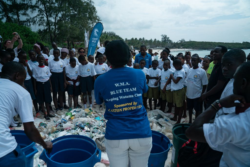 Woman talking to a school group gathered around the plastic trash results of a beach cleanup.