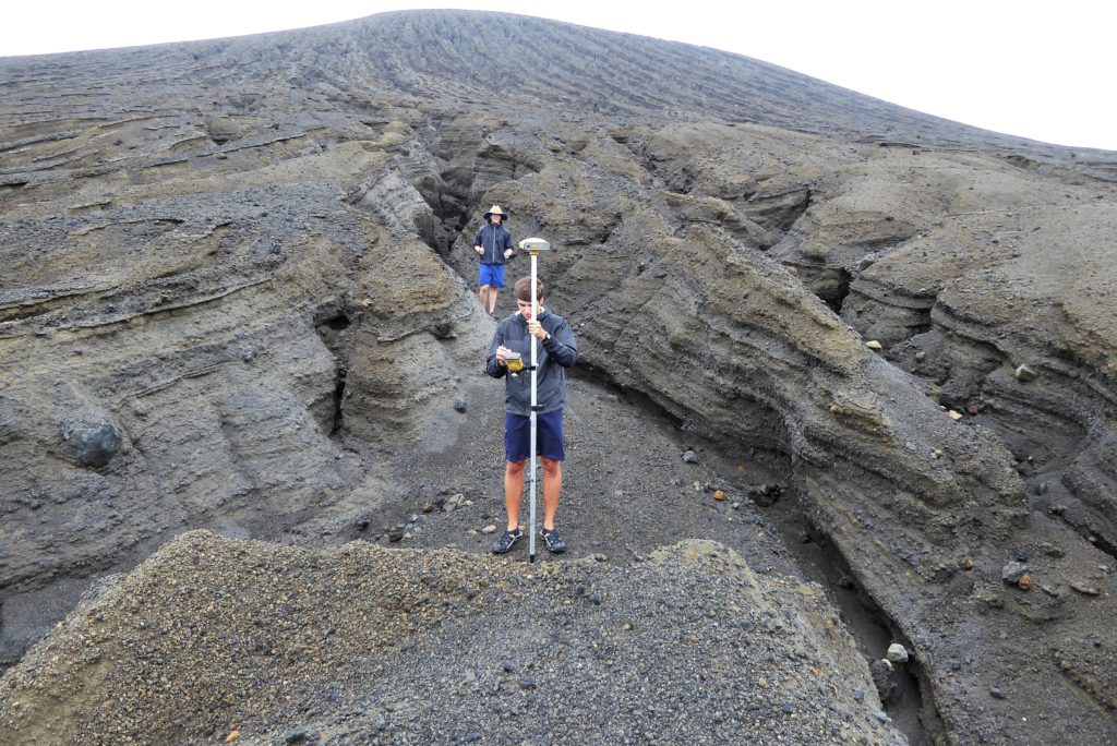Students stand in a deeply eroded gully, taking a measurement.