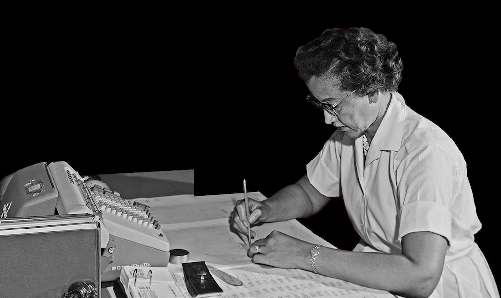 Katherine Johnson working at a desk with a mechanical calculating machine in front of her.