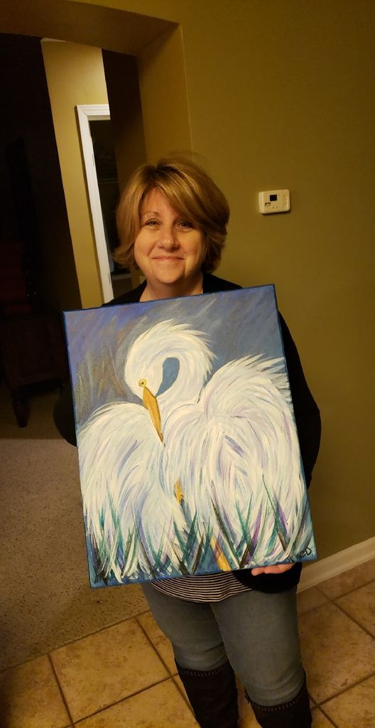 Original picture of Cindi Decker holding her painting of an egret.