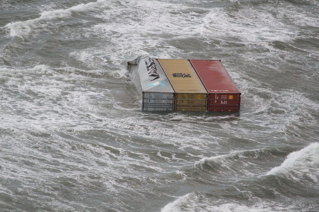 Three containers, one damaged, float in the water.