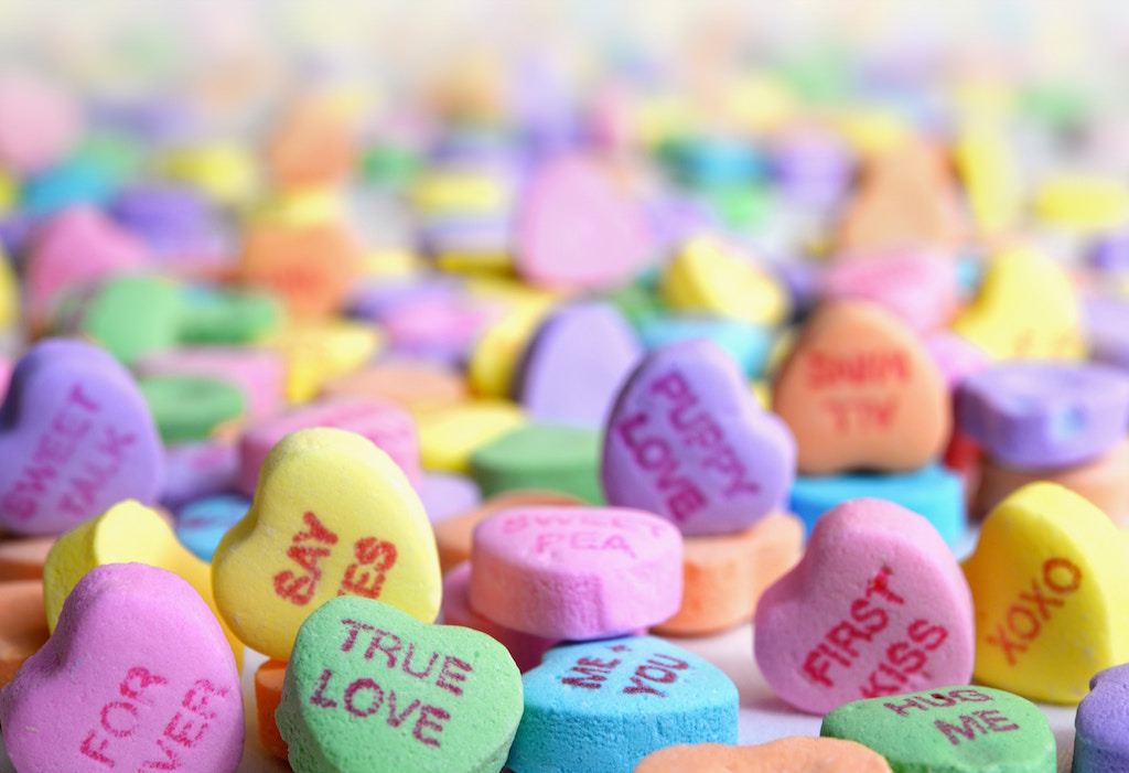 """Close up picture of Sweethearts candies, with phrases such as """"True Love"""", """"Say Yes"""", and """"Puppy Love"""" visible."""