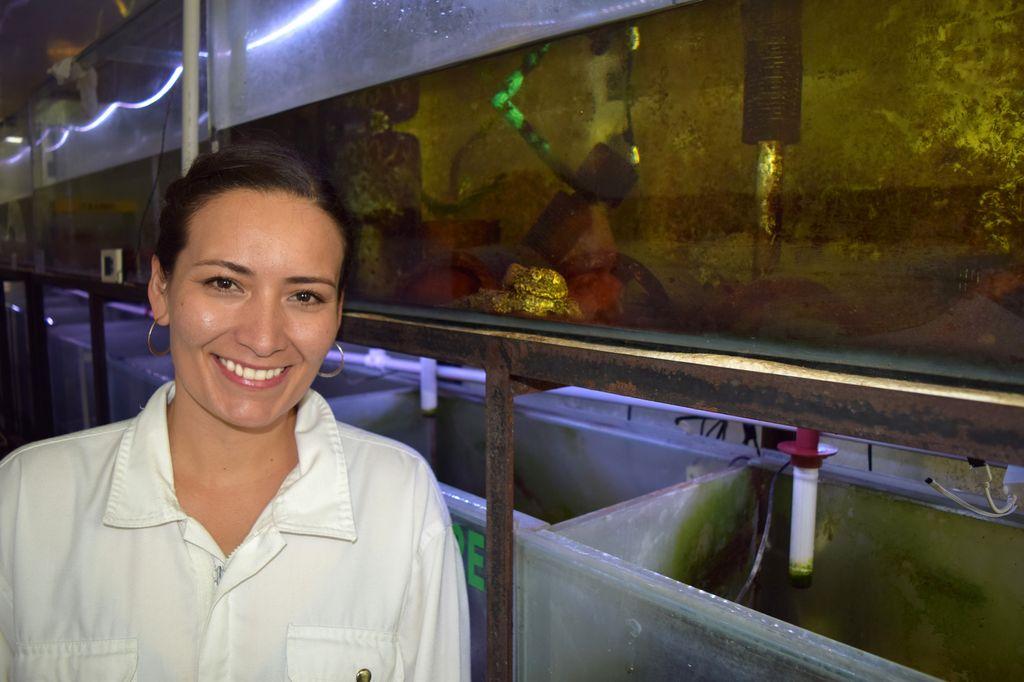 Teresa Camacho poses in front of aquariums.