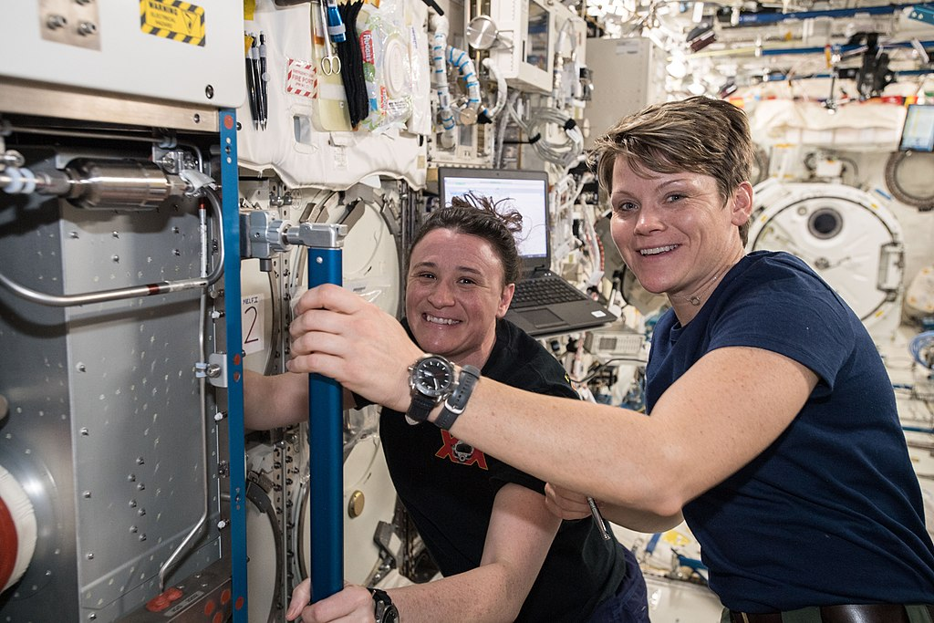 NASA astronauts Serena Auñón-Chancellor (background) and Anne McClain work inside the Japanese Kibo laboratory module cleaning vents to maintain air circulation aboard the International Space Station.