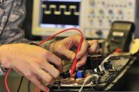 U.S. Army Pfc. John Howard fixes a public address system.