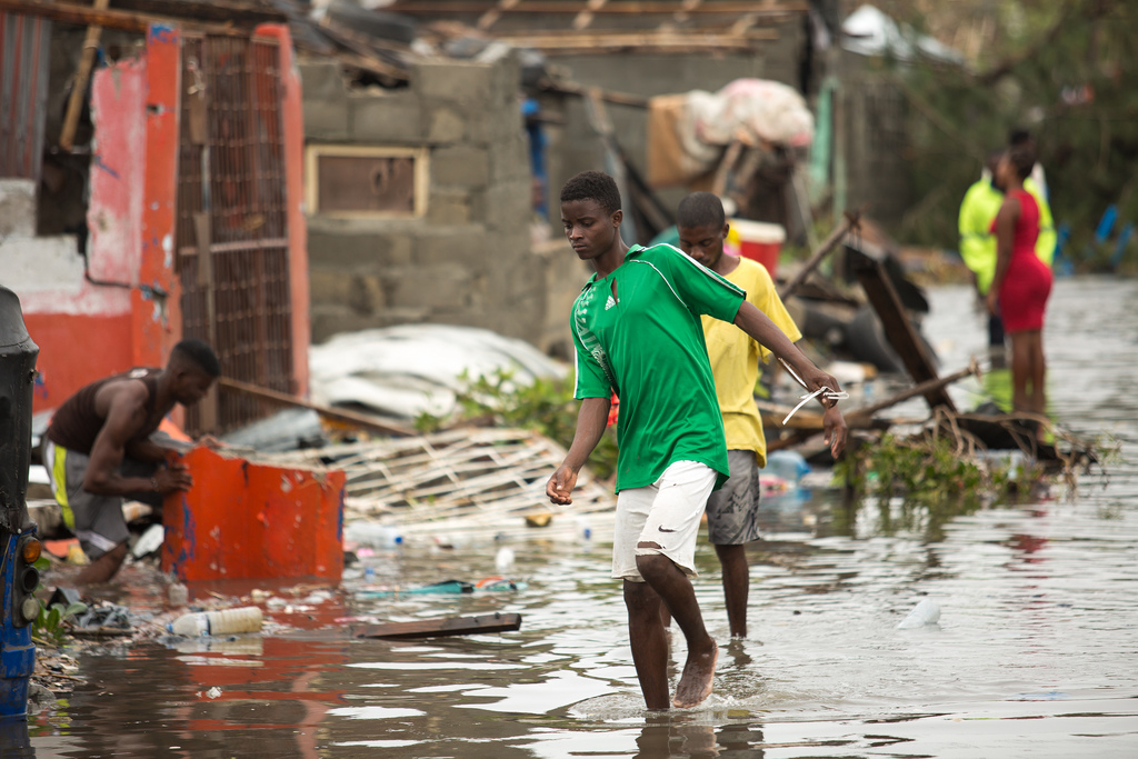 Boys wading through water as people try to rebuild their homes.