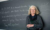 Karen Uhlenbeck in front of a chalkboard
