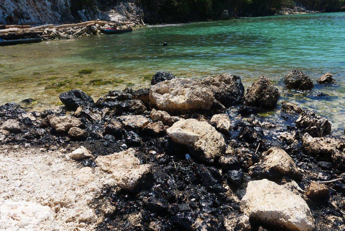 Oil covered rocks on beach.