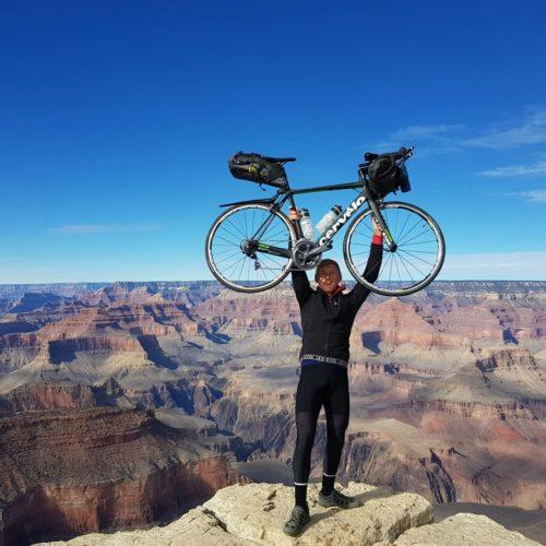 Charlie raises bike overhead with Grand Canyon backdrop.