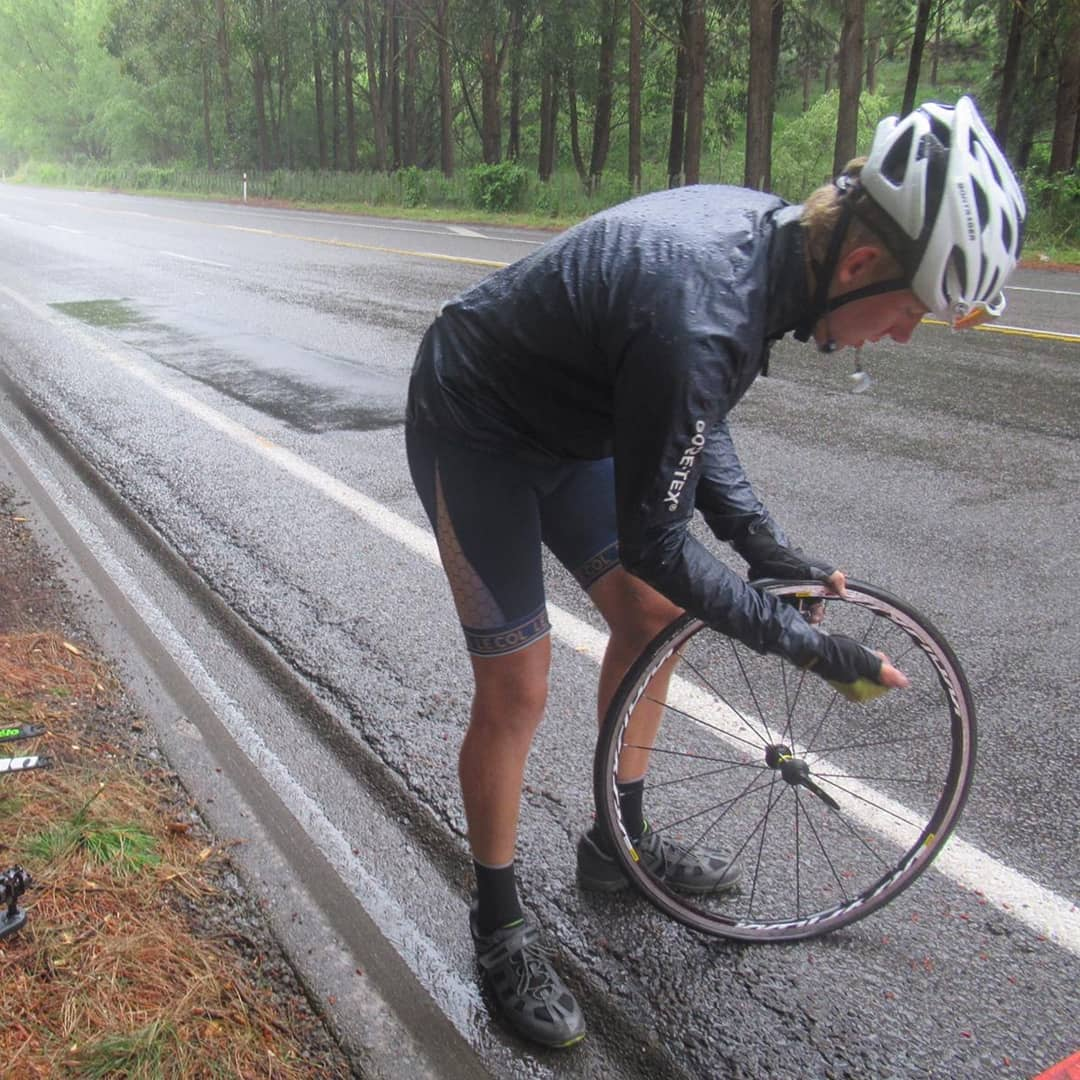 Charlie fixing a flat tire by the side of the road.