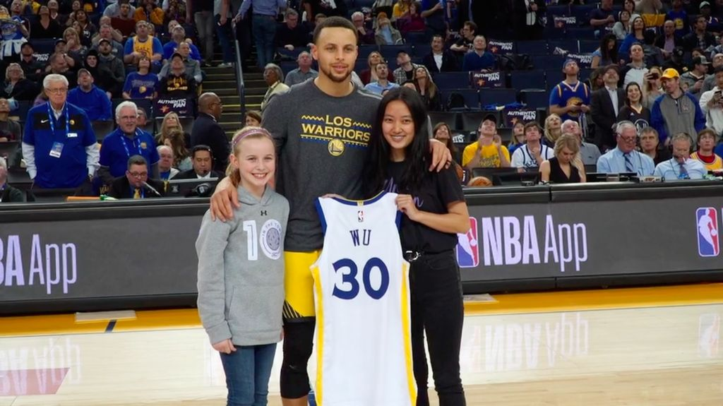 Riley Morrison, Stephen Curry, and Vivian Wu stand at center court.