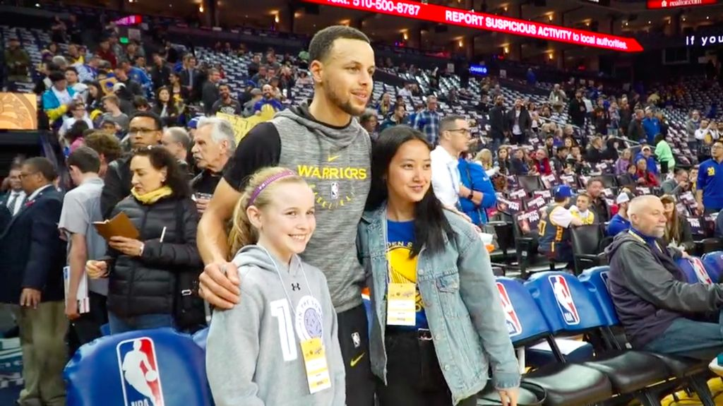 Riley Morrison, Stephen Curry, and Vivian Wu stand by the sidelines.