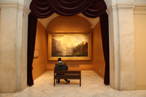 Seated person viewing painting in the second floor galleries at the Smithsonian American Art Museum