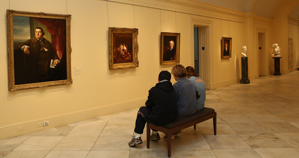 Three people seated on a bench on the second floor galleries at the Smithsonian American Art Museum
