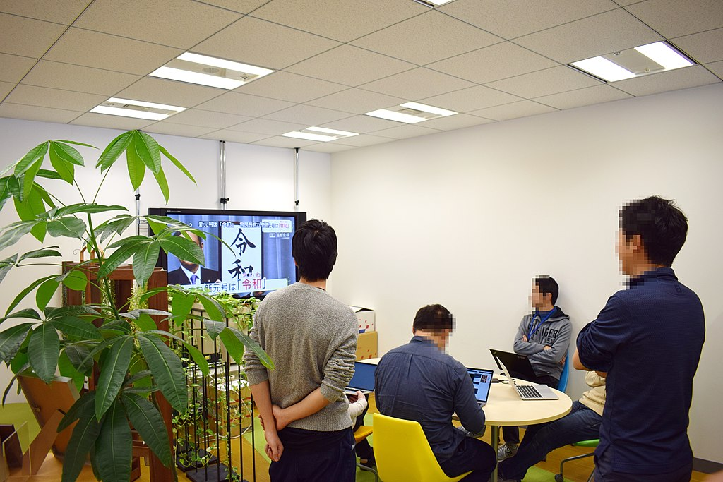 Japanese office workers taking a break to watch the name of the new era being announced on TV