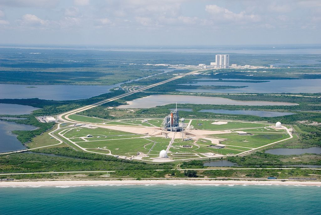 An aerial view of part of the Kennedy Space Center's giant complex featuring the Space Shuttle Endeavour and its support stack of hardware on launch pad 39A