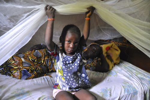 Mother and child under a bednet near Kita, Mali. October 2013. Photographer: Jane Silcock