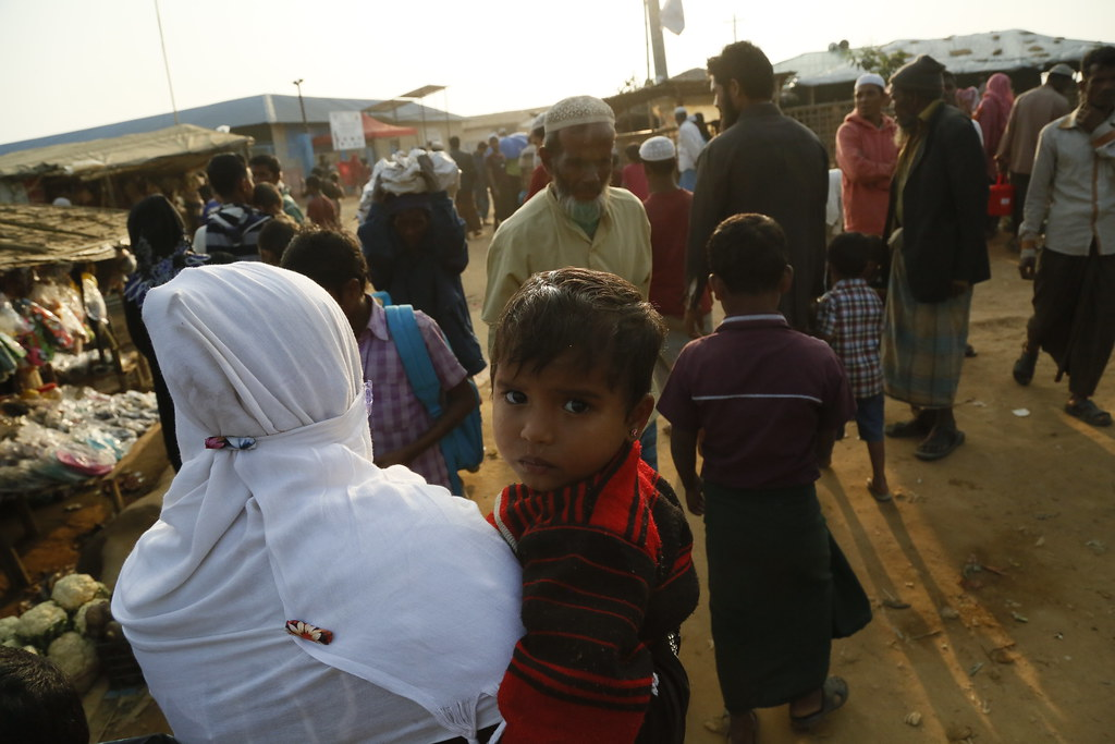 A young child looks anxiously at the camera as his mum takes him to a clinic to be checked for diphtheria in the Kutupalong camp for Rohingya refugees in Bangladesh, January 2018.