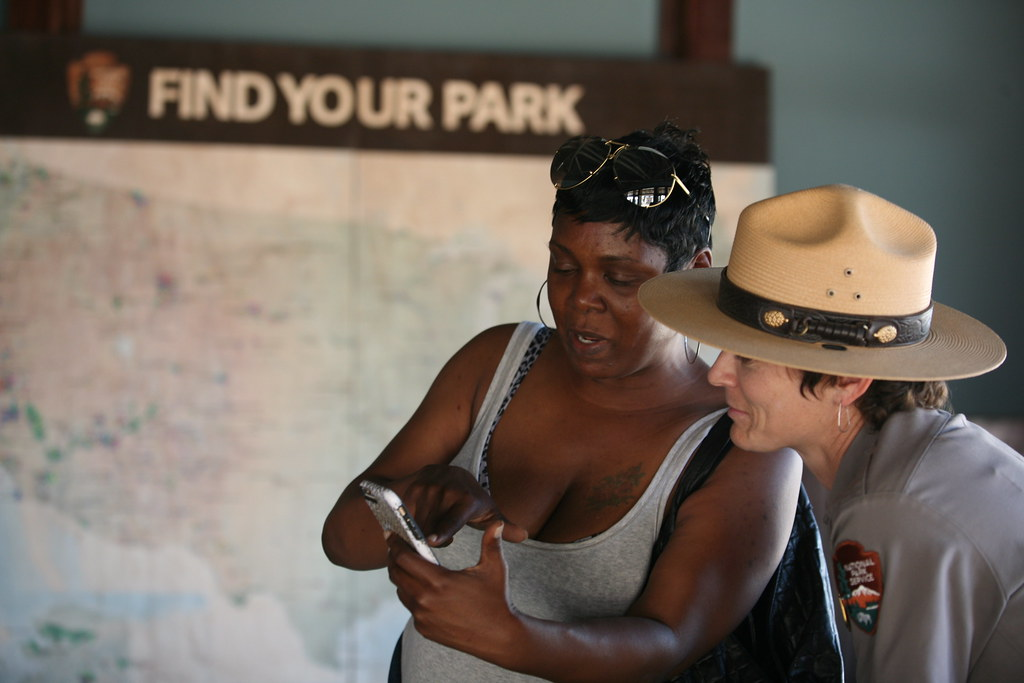 Woman and park ranger looking at phone