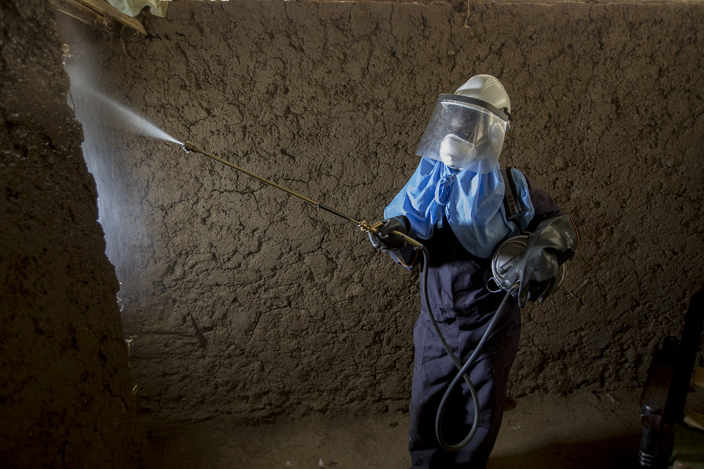 A woman in protective gear sprays a house for mosquitoes. The sprayer, Caroline Obinju Ocholla, is 33 yrs old, married with 4 children - 5,8,10, and 12 years old. She currently volunteers as a CHV. Photo by Jessica Scranton/AIRS