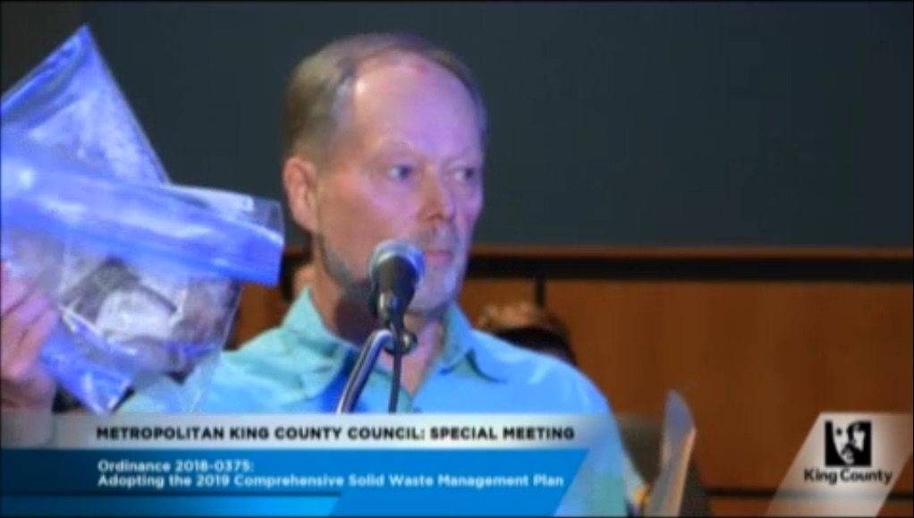 Dave Vogel holds up a bag of human at the King County counselor