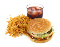 A basic and popular Fast food meal, which includes a burger, french fries and a drink.