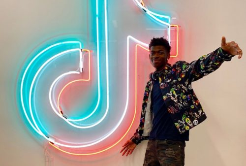 Lil Nas X in front of a neon sign at TikTok.