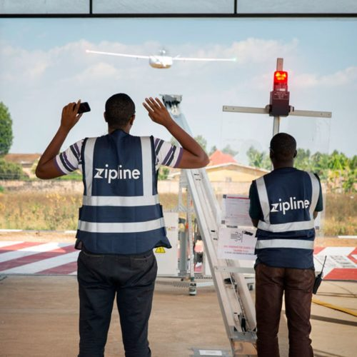 Workers watch as a drone takes off from a catapult.