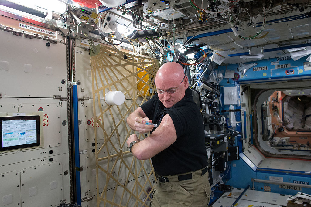 NASA astronaut Scott Kelly gives himself a flu shot for an ongoing study on the human immune system. The vaccination is part of NASA's Twins Study.