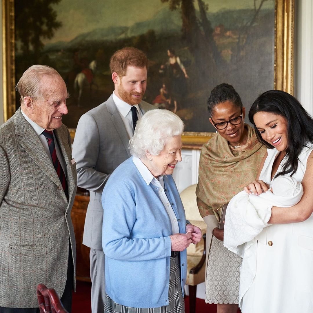 The Queen of England meets her great-grandson, held by his mother, Meghan Markle.