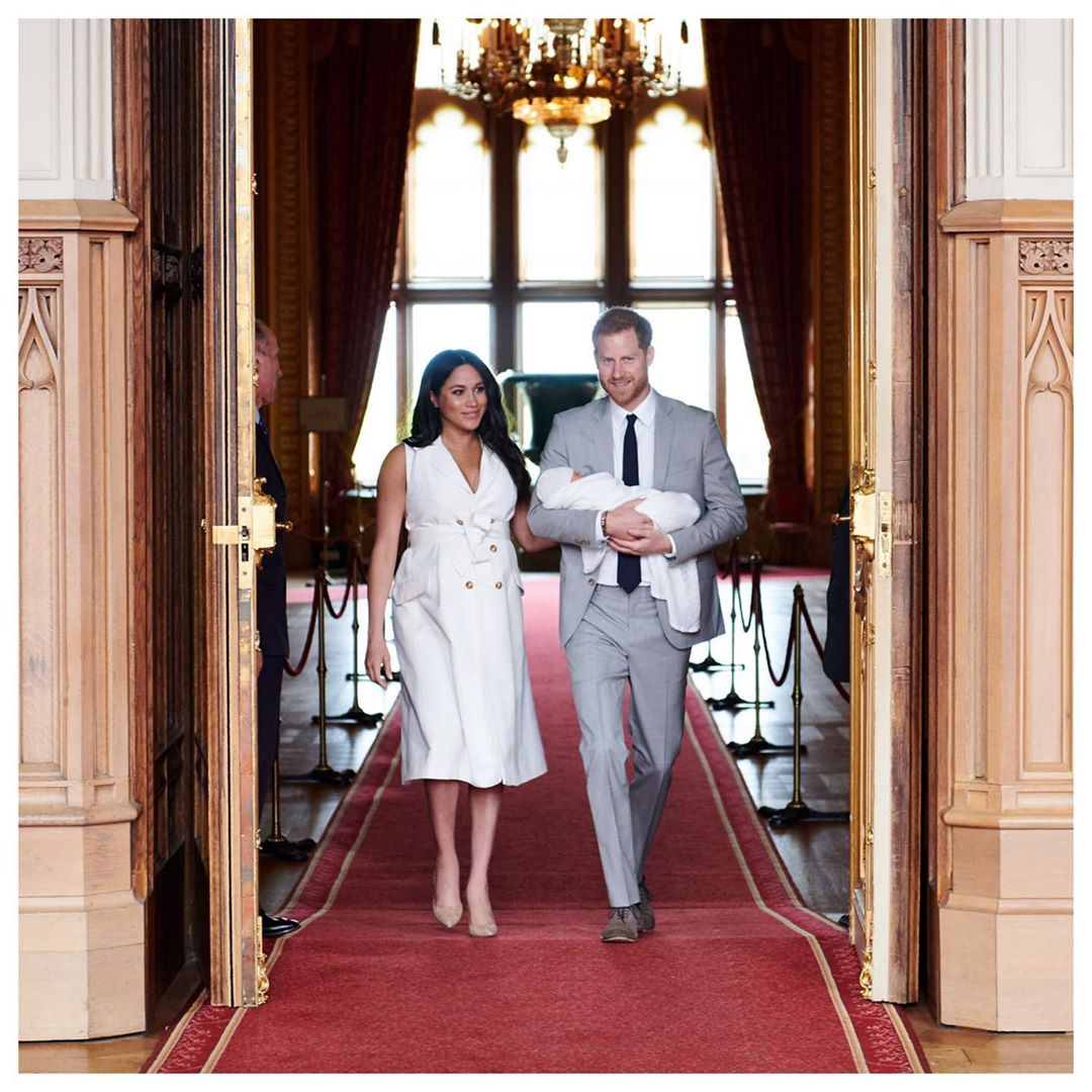 The Duke and Duchess of Sussex walking through a doorway with their baby.