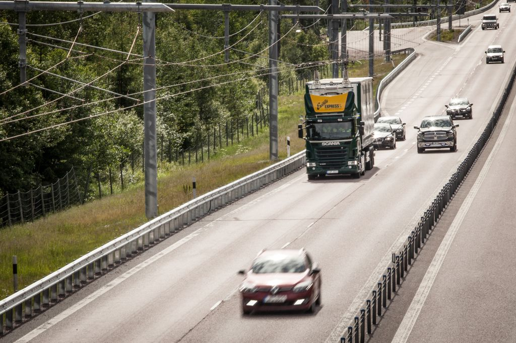 A hybrid truck travels on an eHighway, charging from an overhead cable system.