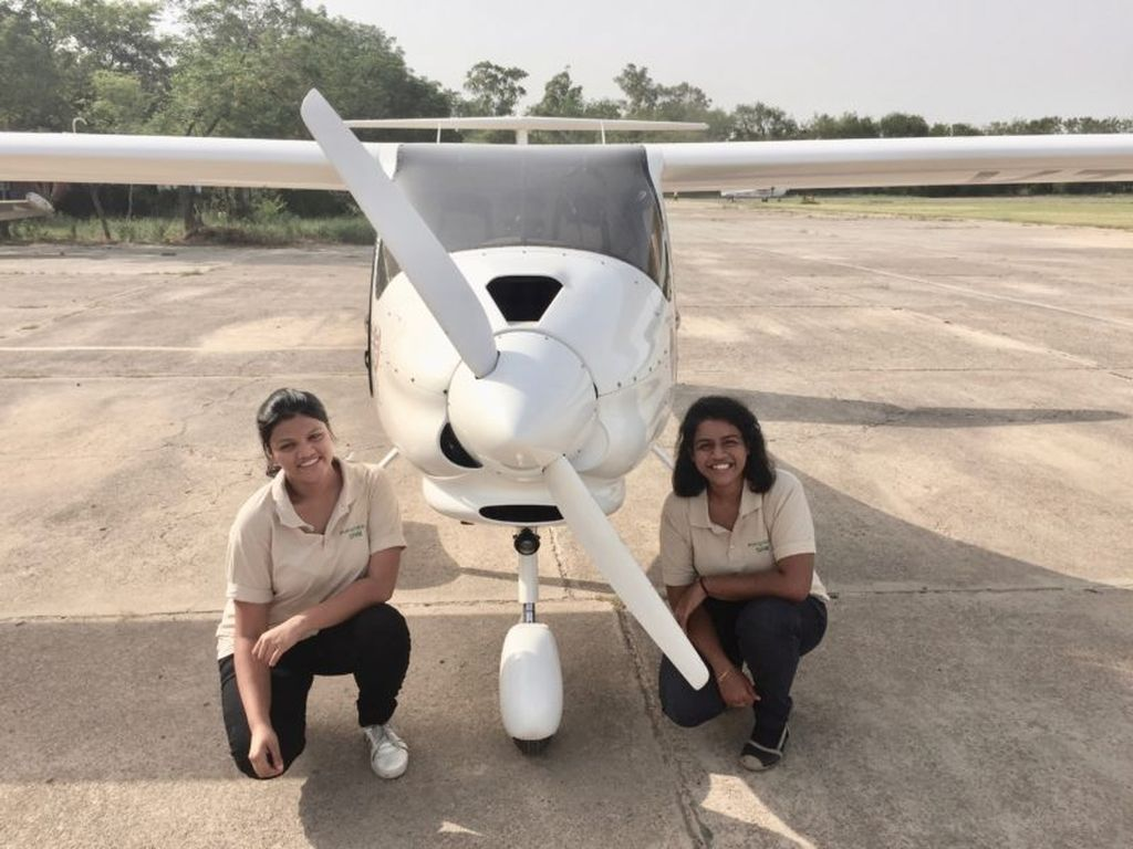 Aarohi Pandit and Keithair Misquitta in front of light sport aircraft.