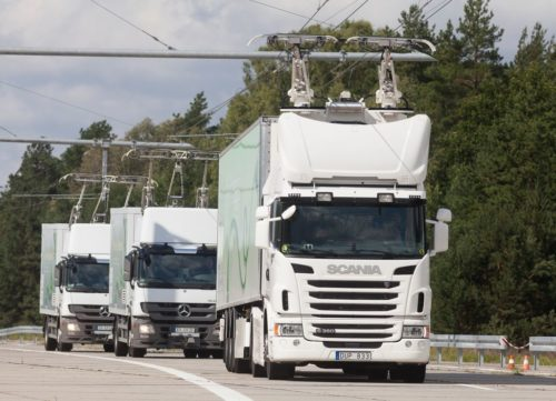 Three hybrid trucks travel on an eHighway, charging from an overhead cable system.