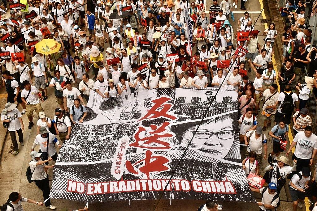 "Protesters in white hold sign saying ""No extradition to China"" - (繁體): 香港民陣估計103萬人參與6-9反送中大遊行。(美國之音湯惠芸拍攝)"