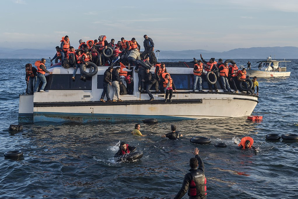 Syrian and Iraqi refugees arrive from Turkey to Skala Sykamias, Lesbos island, Greece. Volunteers (life rescue team - with yellow-red clothes) from the Spanish NGO Proactiva Open Arms help the refugees.