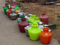 Bright multi-coloured water pots lined up to be filled at the street tap. These bright plastic jugs are ubiquitous in Chennai and Tamil Nadu.