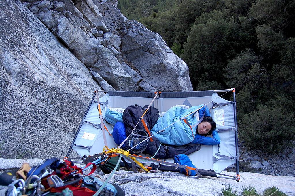 A woman lying on a portaledge.