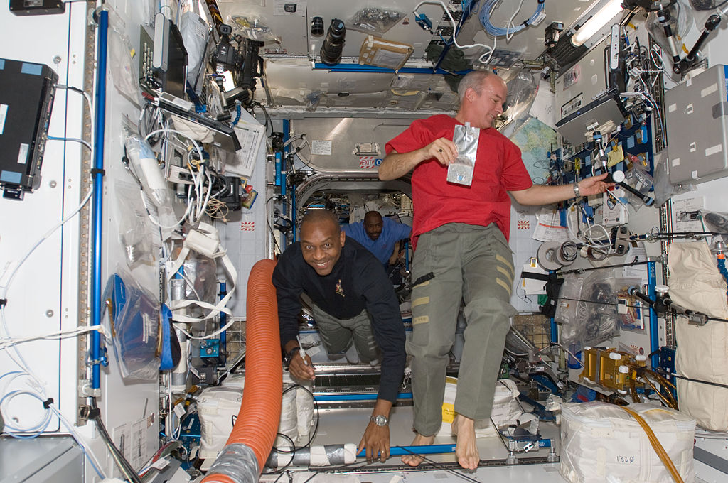 Astronauts Robert L. Satcher Jr. (left), STS-129 mission specialist; and Jeffrey Williams, Expedition 21 flight engineer, are pictured in the Harmony node of the International Space Station while Space Shuttle Atlantis remains docked with the station. Astronaut Leland Melvin, STS-129 mission specialist, is visible in the background.