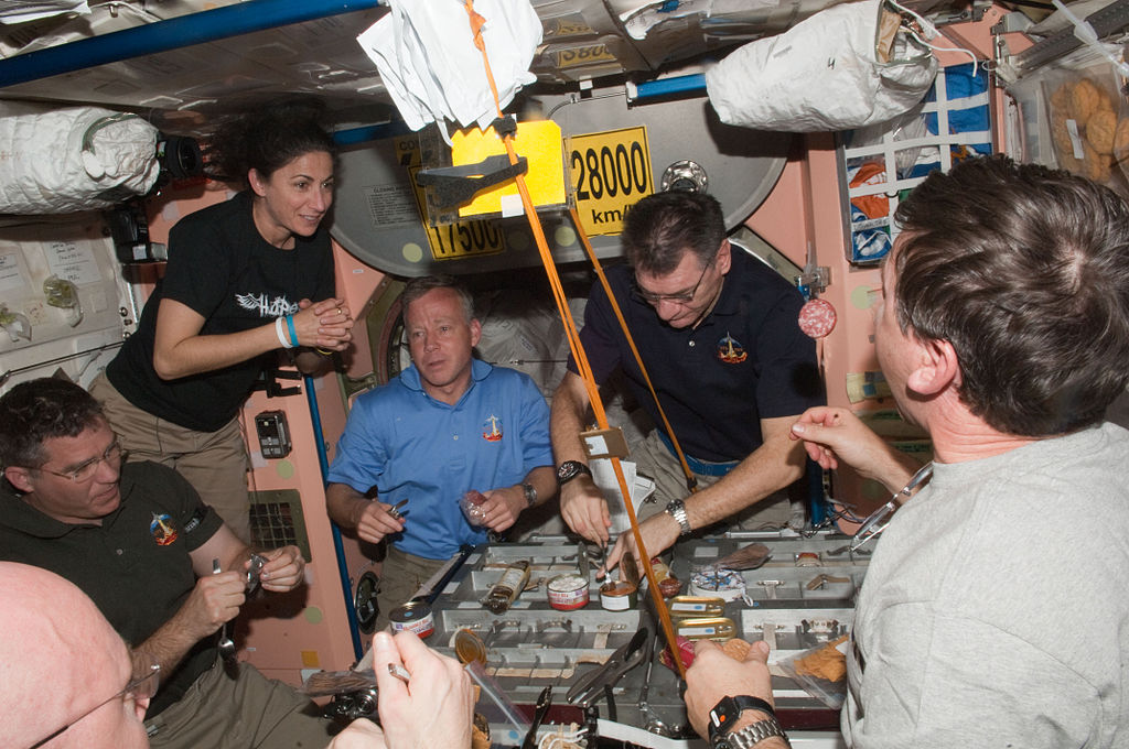Expedition 26 and STS-133 crew members share a meal in the Unity node of the International Space Station while space shuttle Discovery remains docked with the station.