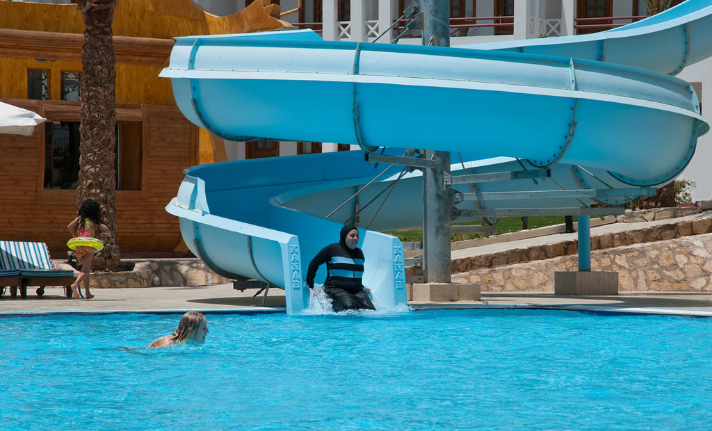 Woman in a burkini going down a water slide.