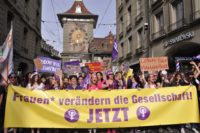 Women marching with signs in the June 14 Women's Strike in Switzerland.