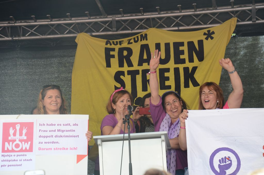 Women on a podium gesture at the Frauenstreik.